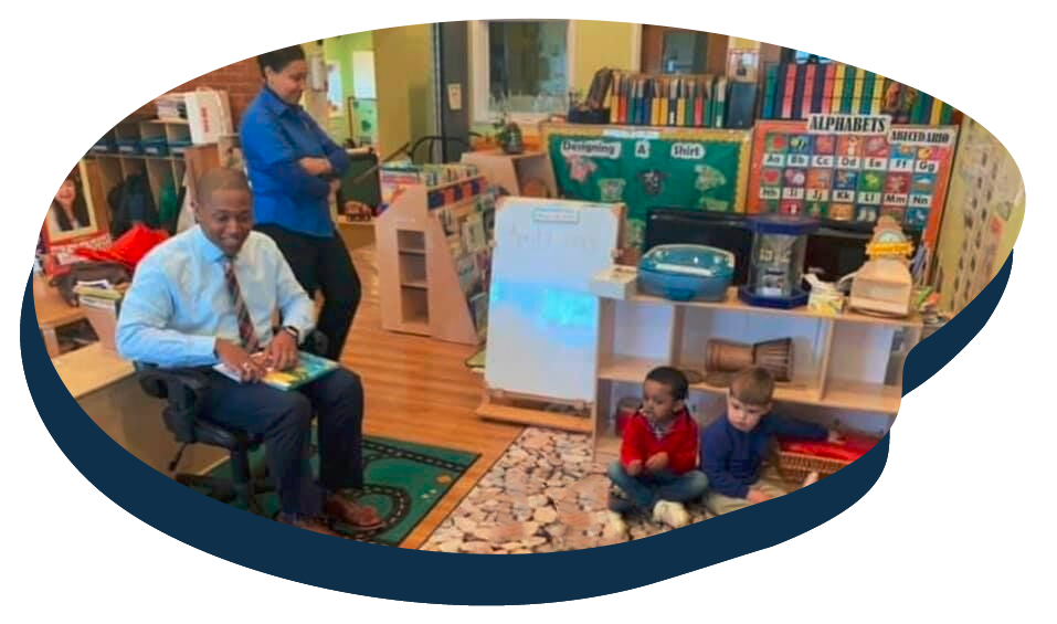 Teacher preparing to read a storytelling books to group of children inside classroom at a Preschool & Daycare Serving Washington, DC