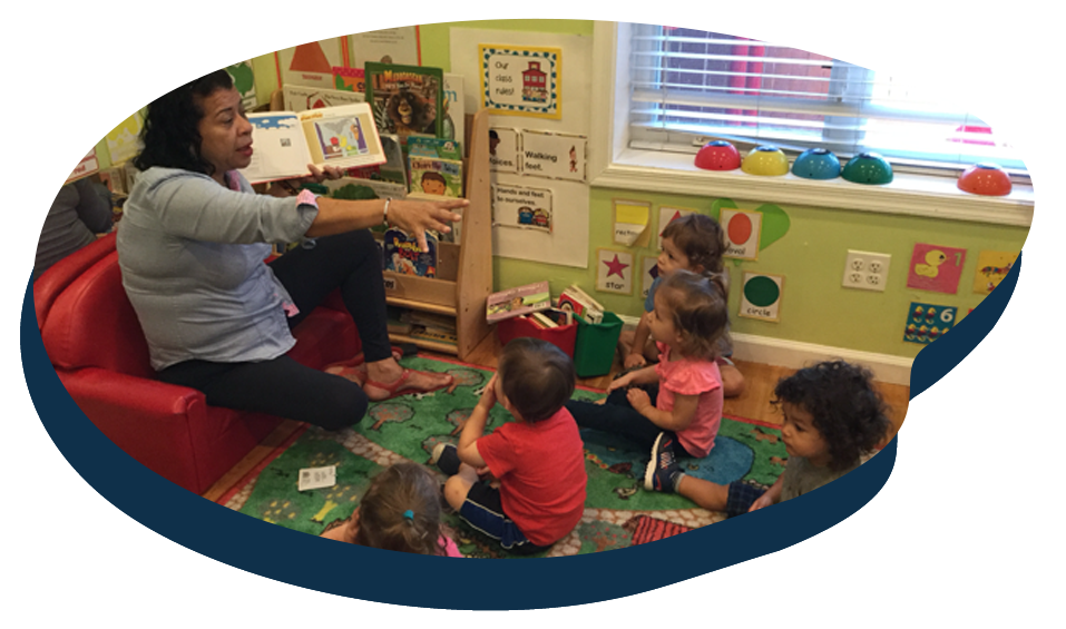 Teacher reading a storytelling books in front of children at a Preschool & Daycare Serving Washington, DC