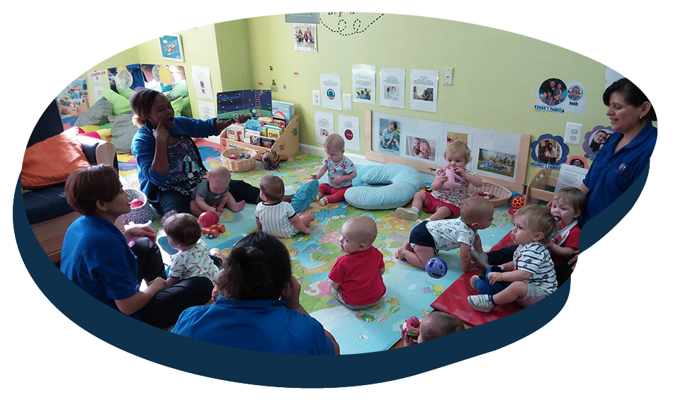 Group of toddlers inside nursery, playing with teachers at a Preschool & Daycare Serving Washington, DC