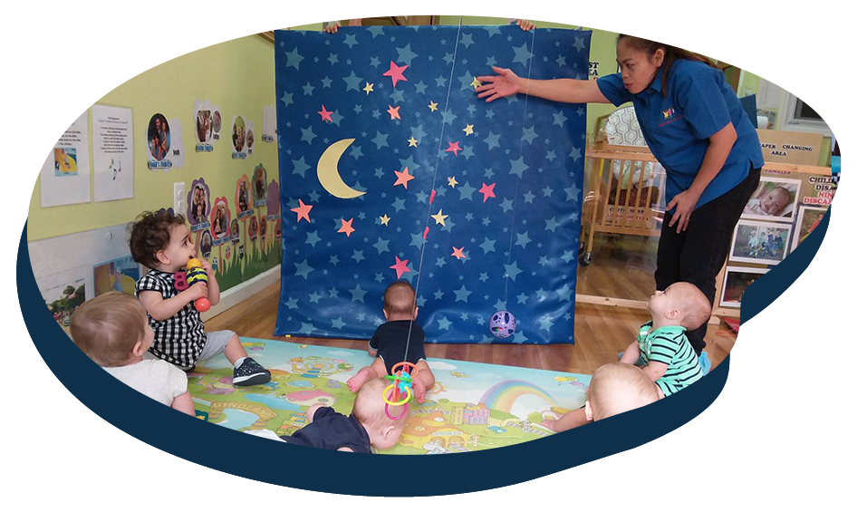 Teacher showing group of babies colorful stars and moon, early developmental activity, at a Preschool & Daycare Serving Washington, DC