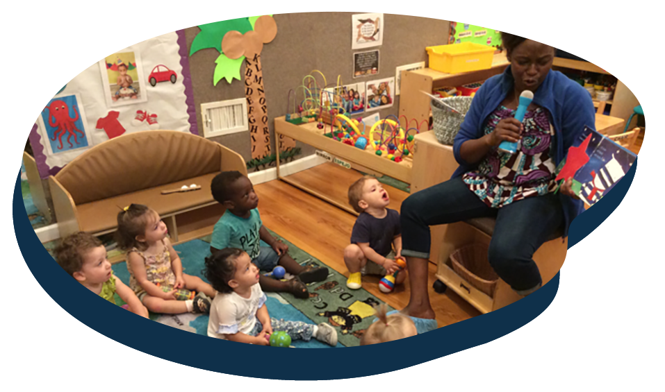 Teacher using a microphone reading a storytelling book in front of group of toddlers at a Preschool & Daycare Serving Washington, DC