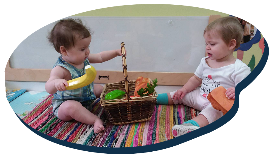 Toddlers playing with plastic toy fruits, sitting on the floor inside nursery room, early developmental at a Preschool & Daycare Serving Washington, DC