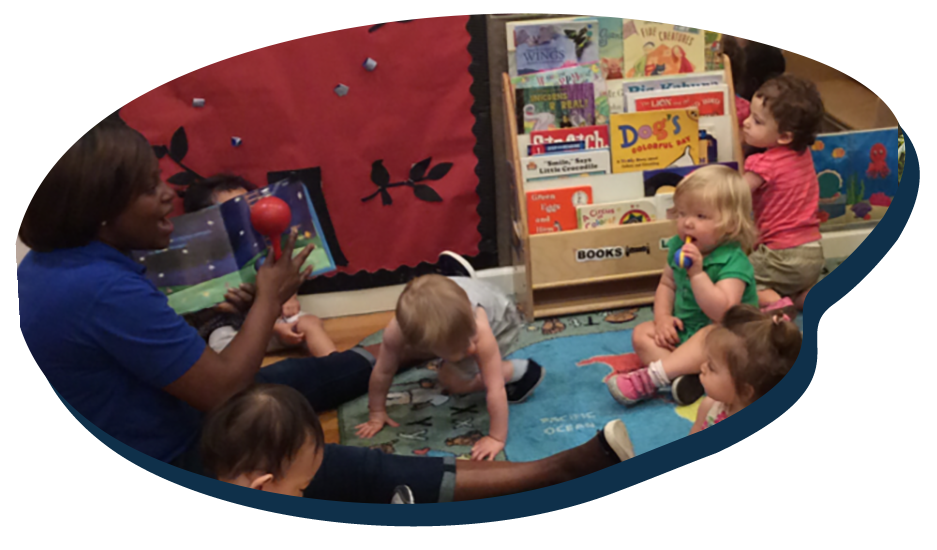 African american teacher showing and playing to group of toddlers percussion musical instruments at a Preschool & Daycare Serving Washington, DC