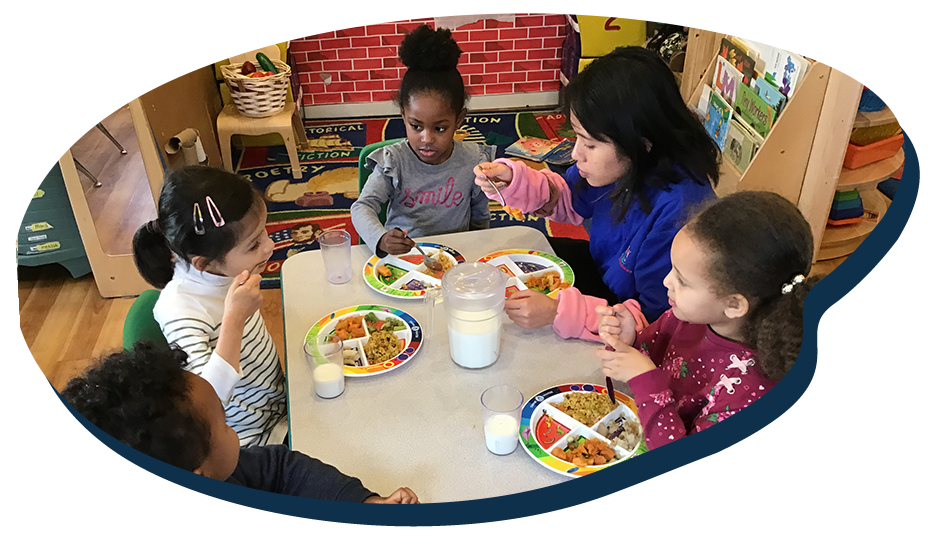 Diverse group of young little kids enjoy eating with teacher at a Preschool & Daycare Serving Washington, DC