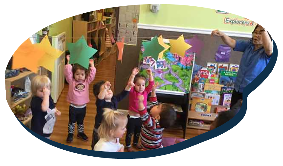 Group of little young children raising their hands to get the colorful paper stars hanging on a string held by a teacher at a Preschool & Daycare Serving Washington, DC