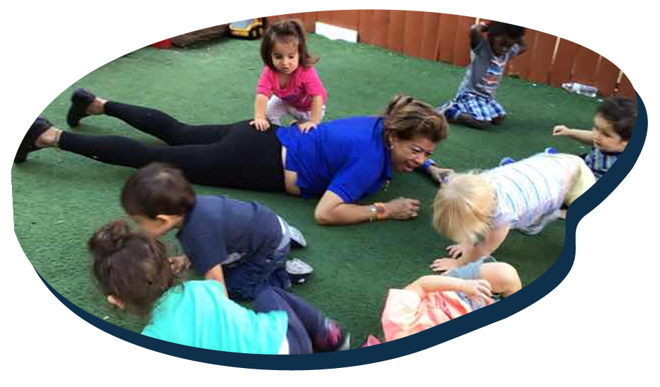 Teacher lying face down with young little little preschool children playing around and crawling at a Preschool & Daycare Serving Washington, DC