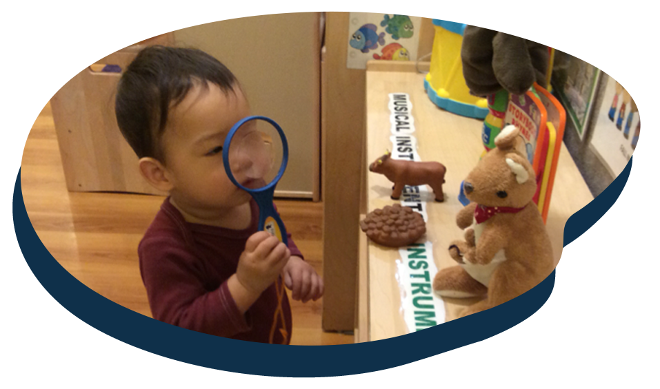 Young little Asian toddler looking through a magnifying glass for a science activity, early child developmental at a Preschool & Daycare Serving Washington, DC