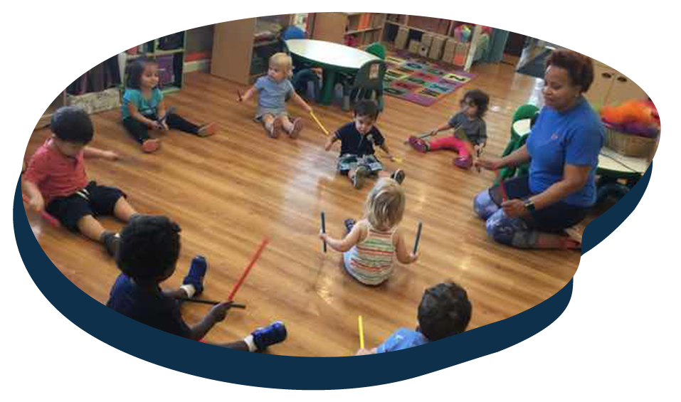 Diverse group of toddlers sitting on the floor while holding colorful sticks in their hands following teachers instructions at a Preschool & Daycare Serving Washington, DC
