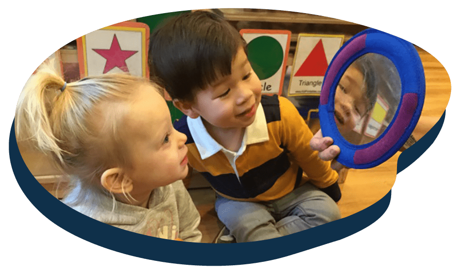 Cute little toddlers playing with a mirror, early developmental at a Preschool & Daycare Serving Washington, DC