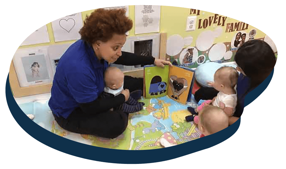 Teachers with babies on their lap t a Preschool & Daycare Serving Washington, DC