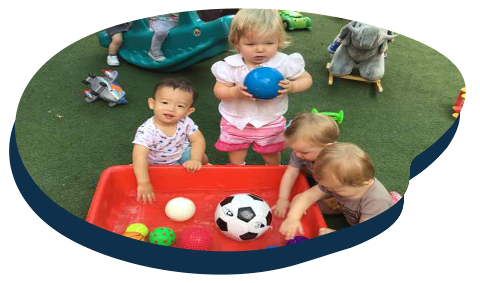Group of diverse toddlers playing with different kinds of sports ball on a playground at a Preschool & Daycare Serving Washington, DC