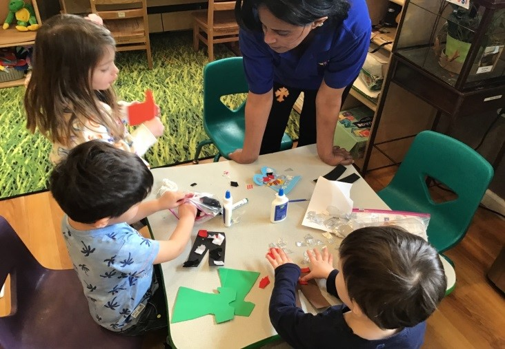 Teacher helping young little kids with art projects, cutting and pasting at a Preschool & Daycare Serving Washington, DC
