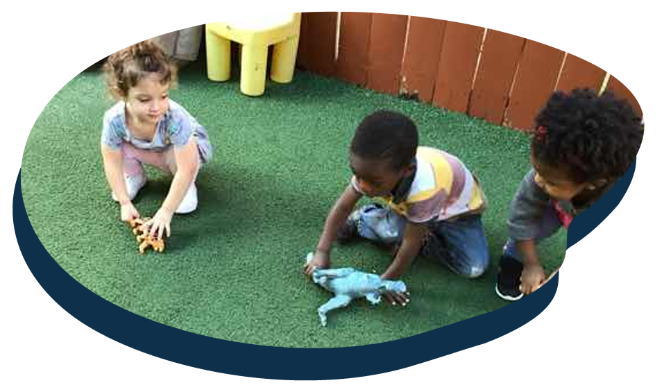 Diverse little kids playing with toy dinosaur at a Preschool & Daycare Serving Washington, DC