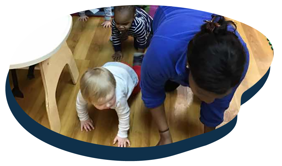 Teacher with babies crawling , developmental activity at a Preschool & Daycare Serving Washington, DC