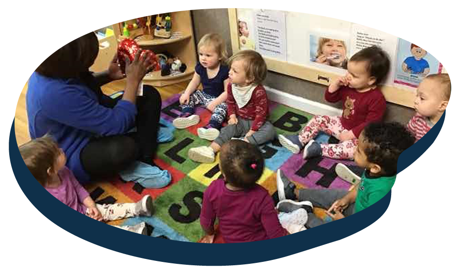 Teacher showing group of diverse toddlers a red balloon heart, early child care, early developmental at a Preschool & Daycare Serving Washington, DC