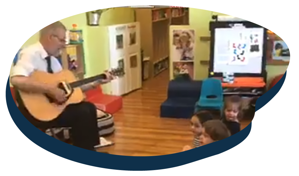 Teacher playing guitar in front of children in music activity at a Preschool & Daycare Serving Washington, DC