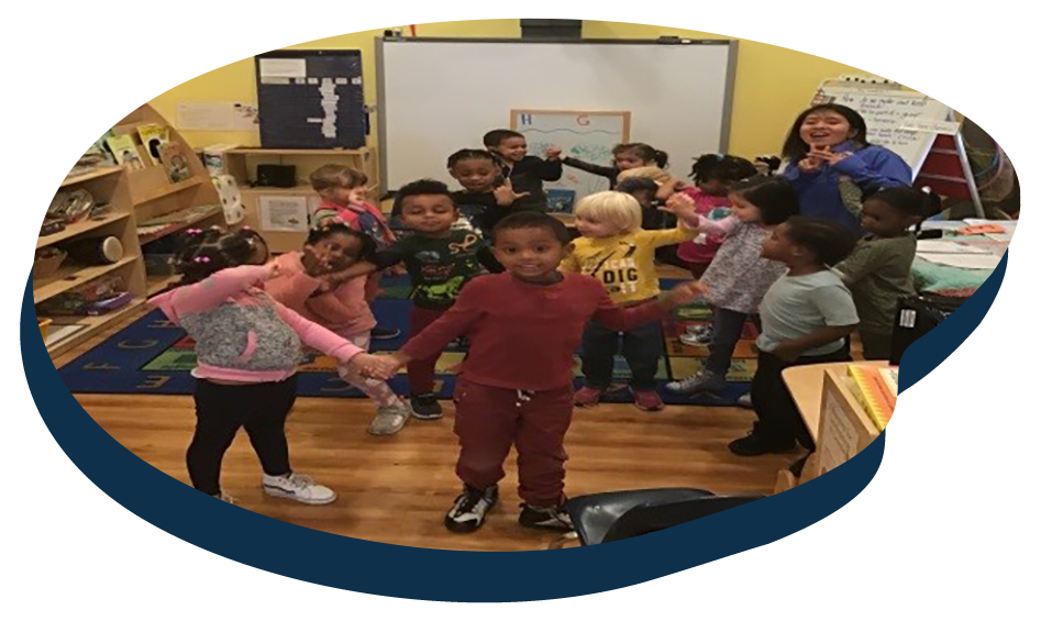 Happy children playing with teacher developmental activity at a Preschool & Daycare Serving Washington, DC