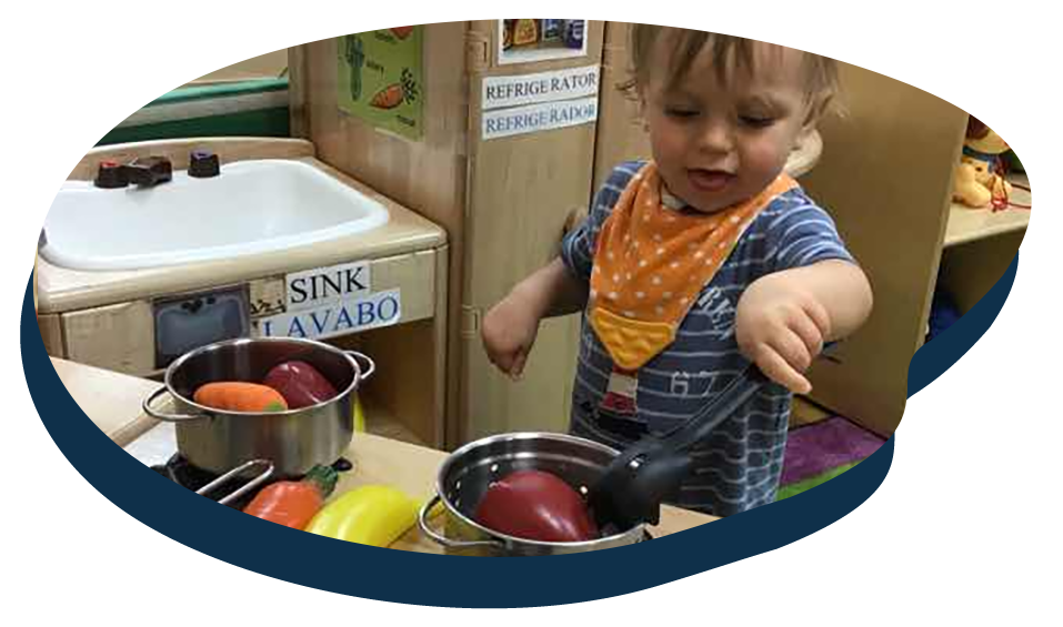 Toddler playing with plastic vegetable toys , cooking activity, developmental for kids at a Preschool & Daycare Serving Washington, DC