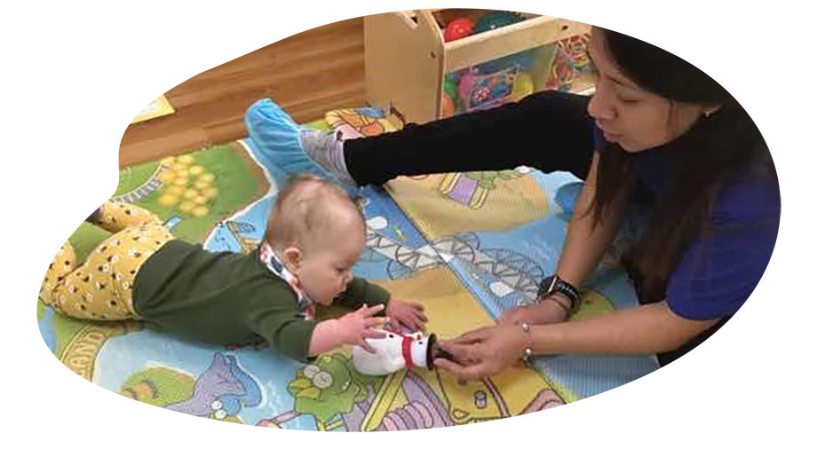 Teacher with baby crawling playing with a snowman toy at a Preschool & Daycare Serving Washington, DC