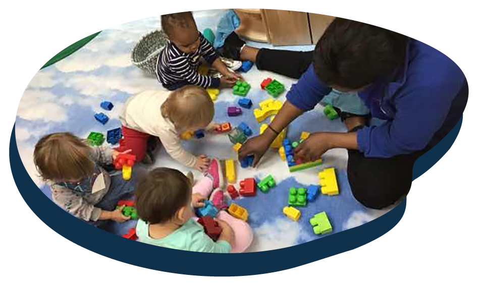 Toddlers with teacher playing with educational building blocks at a Preschool & Daycare Serving Washington, DC