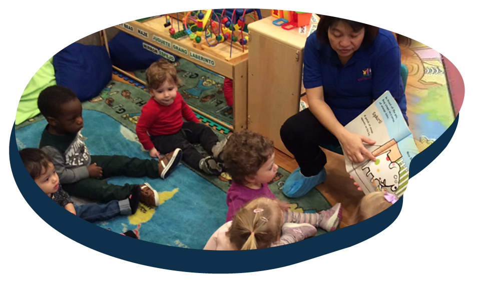 Teacher reading a storytelling book in front of diverse group of toddlers at a Preschool & Daycare Serving Washington, DC