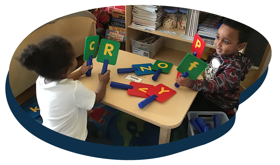 Two African american boy and girl toddler familiarizing with Alphabet letters on a tale inside classroom at a Preschool & Daycare Serving Washington, DC