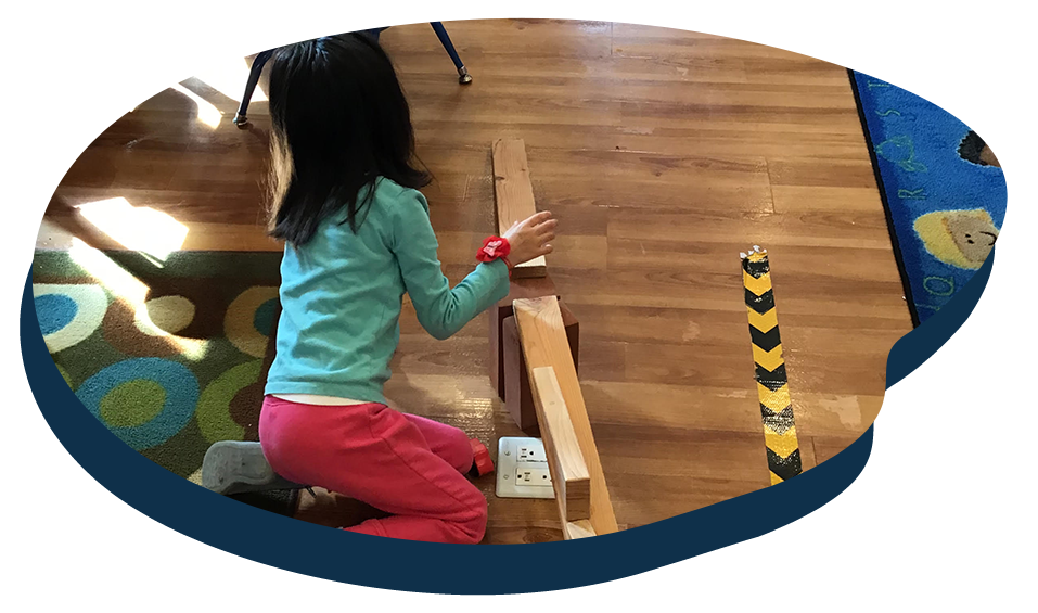 Little kid girl playing with long wooden building blocks at a Preschool & Daycare Serving Washington, DC
