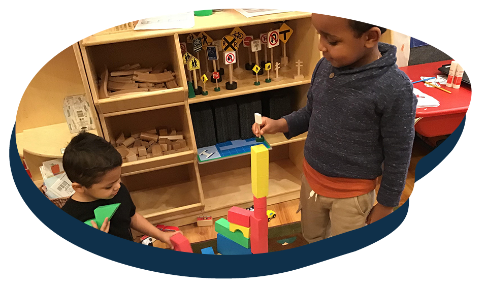 African american and a Hispanic kids playing with colorful building blocks at a Preschool & Daycare Serving Washington, DC