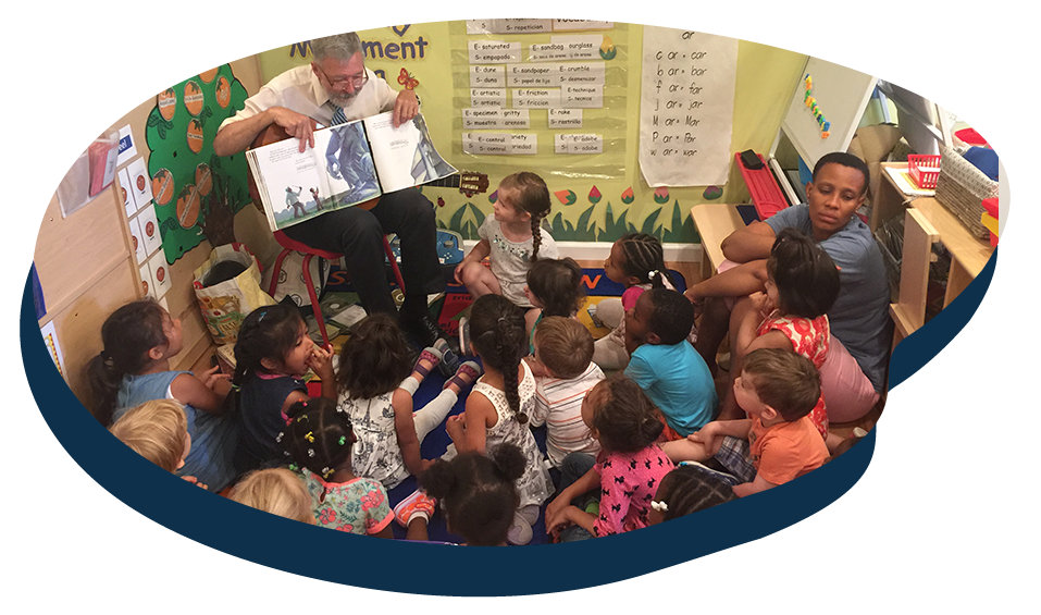 Teachers reading a storytelling books in front of little kids in a classroom at a Preschool & Daycare Serving Washington, DC
