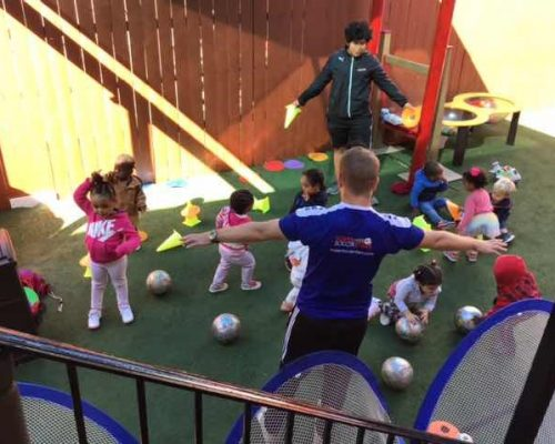 group of toddlers with teacher coaching enjoy playing soccer balls at school playground at a Preschool & Daycare Serving Washington, DC