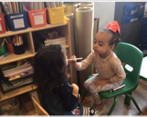 Young little african american kid girl putting face paint on another preschool kid girl, engagement activity, at a Preschool & Daycare Serving Washington, DC