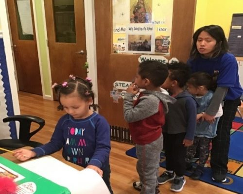 Teacher helping preschool kids fall in line, showing courtesy and discipline at a Preschool & Daycare Serving Washington, DC