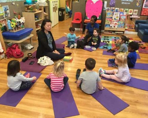 Asian teacher in front of young little kids preparing for yoga at a Preschool & Daycare Serving Washington, DC