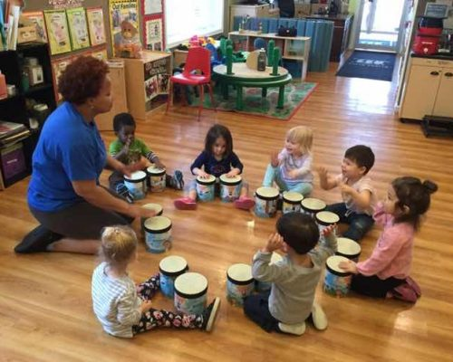 Group of diverse young little kids in music class, learning to play drums with African american teacher at a Preschool & Daycare Serving Washington, DC