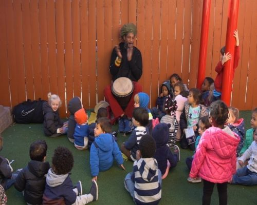 A local playing percussion in front of children, at a Preschool & Daycare Serving Washington, DC