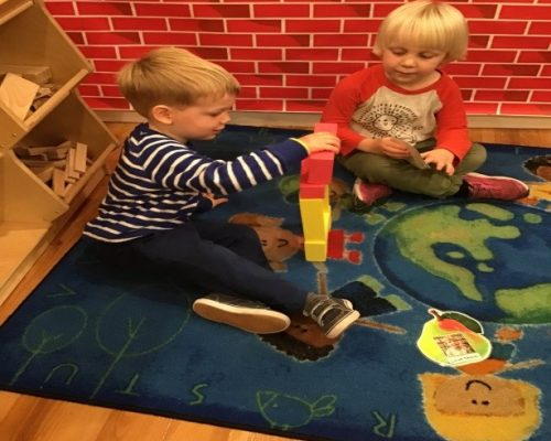 Two young little kids playing with building blocks, developmental activity at a Preschool & Daycare Serving Washington, DC