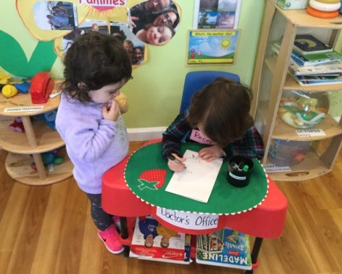 A young little kid drawing on a piece of paper while another is watching her while standing at a Preschool & Daycare Serving Washington, DC