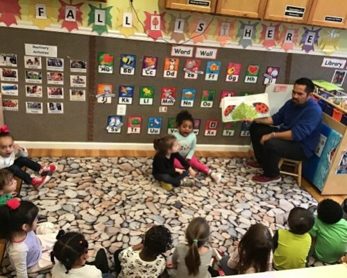 Teacher showing group of toddlers a picture of lady bug and a leaf on a storytelling book at a Preschool & Daycare Serving Washington, DC
