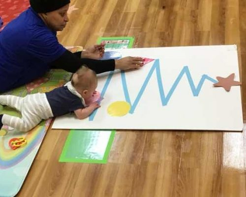 African american teacher and a baby lying face down doing a Christmas art project at a Preschool & Daycare Serving Washington, DC