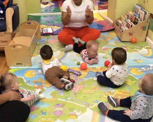 group of toddlers playing with plastic ball while listening to teacher in a nursery room at a Preschool & Daycare Serving Washington, DC