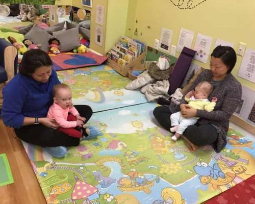 Teachers carrying in their lap some babies playing with them inside nursery room at a Preschool & Daycare Serving Washington, DC