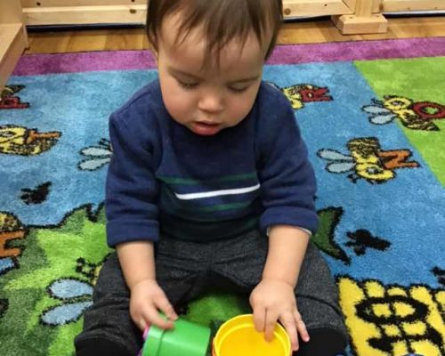 A young little one playing with colorful plastic small containers , early developmental at a Preschool & Daycare Serving Washington, DC