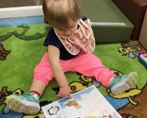 A young little toddler girl reading a storytelling book at a Preschool & Daycare Serving Washington, DC