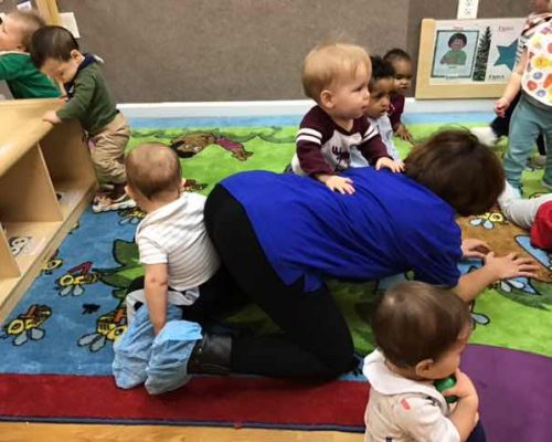 Group of toddlers playing on a carpet with their teacher inside room at a Preschool & Daycare Serving Washington, DC