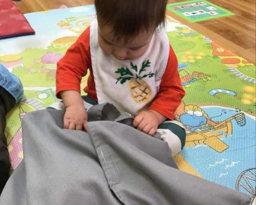 Little toddler boy playing with a gray pillow at a Preschool & Daycare Serving Washington, DC