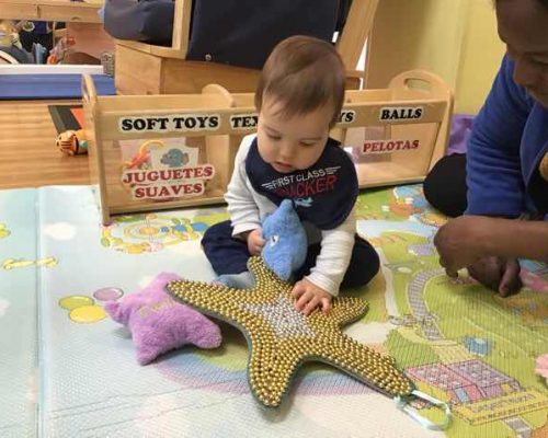 A young little ones playing with toy starfish assisted by an a teacher t a Preschool & Daycare Serving Washington, DC
