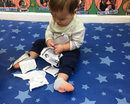 A toddler boy playing with papers , tearing the them at a Preschool & Daycare Serving Washington, DC
