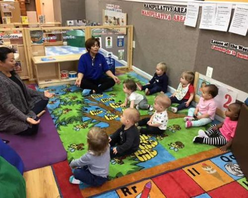 Teachers showing a yoga posture to group of toddlers , early developmental at a Preschool & Daycare Serving Washington, DC