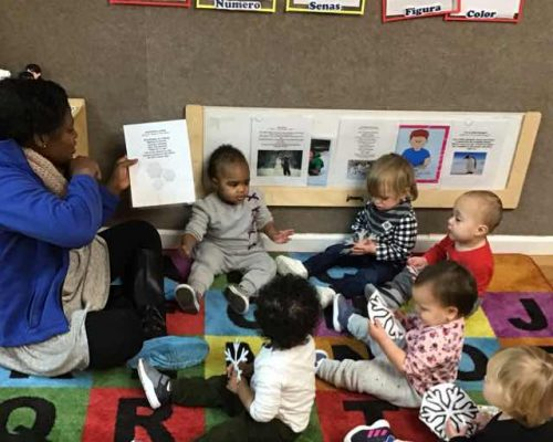 African american teacher reading some instructions to toddlers at a Preschool & Daycare Serving Washington, DC