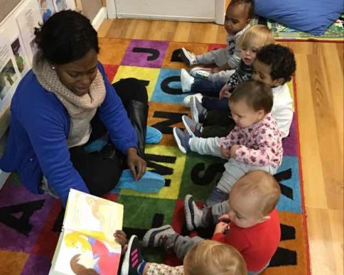 African american teacher reading a storytelling book to toddlers at a Preschool & Daycare Serving Washington, DC